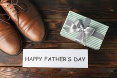 Brown leather shoes, inscription happy fathers day and gift box on wooden background, space for text. And top view stock photo