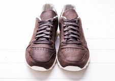 Brown leather shoes with laces on wooden background. With Royalty Free Stock Images