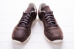 Brown leather shoes with laces on wooden background. With Stock Image