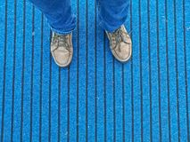 Brown leather shoes with jeans standing on blue carpet stock photo