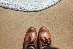 Brown leather shoes near the sea. Looking down on a pair of brown leather shoes standing on a sandy ocean beach. Summer vacation concept Stock Photos