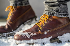 Brown leather shoes in the snow. Shoe Detail. Shallow depth of field. Stock Image