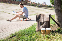 Brown leather shoulder bag with disposable coffee cups and man sitting on skateboard behind. Close-up view of brown leather shoulder bag with disposable coffee Royalty Free Stock Photos