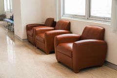 Brown leather sofa chairs inside building Stock Photo
