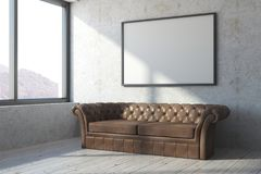 Brown leather sofa in concrete room. Brown leather sofa in concrete interior with picture frame, window and sunlight. Mock up, 3D Rendering Stock Images
