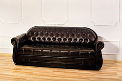 Brown leather sofa near white wall stock photography