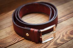 Brown leather strap on wooden board Royalty Free Stock Images