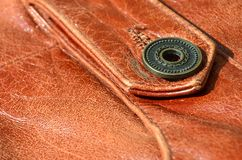 Brown leather texture. Useful as background for any design work. Macro photo of a button on outer clothing made of genuine leathe. R Stock Images