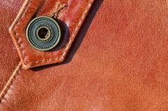 Brown leather texture. Useful as background for any design work. Macro photo of a button on outer clothing made of genuine leathe. R Stock Image