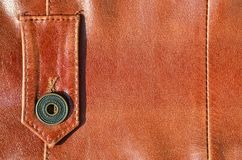 Brown leather texture. Useful as background for any design work. Macro photo of a button on outer clothing made of genuine leathe. R Stock Photos