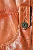 Brown leather texture. Useful as background for any design work. Macro photo of a button on outer clothing made of genuine leathe. R Stock Photo