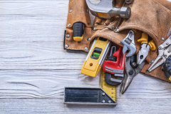 Brown leather tool belt with building implements on wooden board Stock Image
