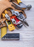 Brown leather toolbelt with construction tools on wood board dir. Ectly above Stock Photo