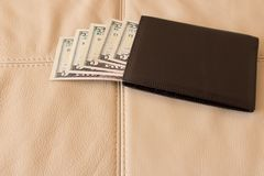 Brown leather wallet with dollars on the background of leather s royalty free stock photos