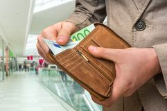 Wallet with euro money in male hands in shopping centre. Brown leather wallet with euro money in male hands in shopping centre Royalty Free Stock Photography