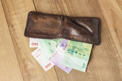 Brown leather wallet with money on wood board background. Photo royalty free stock image