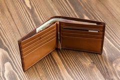Brown leather wallet over dark wooden background. Stock Photos