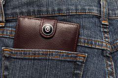 Brown leather wallet in the pocket of jeans. Brown leather wallet in the pocket of American jeans Stock Photos
