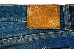 Brown-Lederaufkleber auf Blue Jeans Lizenzfreie Stockfotos