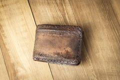 Brown-Ledergeldbörse auf hölzernem Bretthintergrund Stockfotografie