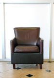 Brown-Lederstuhl auf Fliesenboden stockbilder