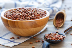 Brown lentils in a wooden bowl and spoon. Stock Image