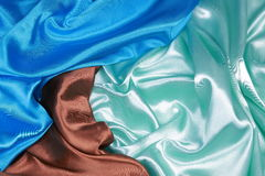 Brown and light green and blue Silk cloth of wavy abstract backg Royalty Free Stock Images