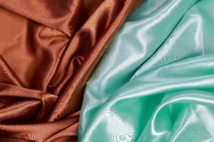 Brown and light green silk satin cloth of wavy folds texture bac Royalty Free Stock Images