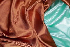 Brown and light green silk satin cloth of wavy folds texture bac Stock Photos
