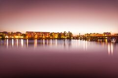 Brown Lighted Buildings Near the Body of Water Landscape Photo Royalty Free Stock Image