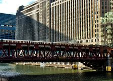 Brown line el train crosses elevated track over the Chicago River alongside the Merchandise Mart. Sunlight glimmers on the water Royalty Free Stock Photography
