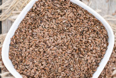 Brown Linseeds. Small portion of brown Linseeds on weathered wooden background royalty free stock photos