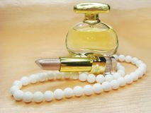 Brown lipstick white beads and perfume Stock Photography