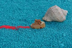 A toy boat sails on the sand with a shell. A brown little toy boat sails on the sand with a shell Royalty Free Stock Images