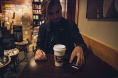 Brown Long Haired Man in Black Jacket Sitting in Front of White Coffee Cup and Phone Stock Photo