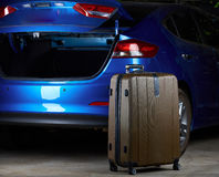Brown luggage suitcase. Standing next to blue modern car with open trunk Royalty Free Stock Photos