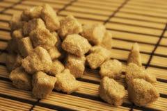 Brown lump sugar. On the bamboo mat Royalty Free Stock Image