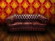 Brown Luxurious armchair. With red golden wallpaper Stock Images