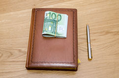Brown luxury notepad with ball pen and some euro banknotes on wooden table Royalty Free Stock Photos