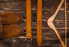 Brown-Männer ` s Stiefel, Ledergürtel und Aufhänger auf hölzernem Hintergrund Stockfotos