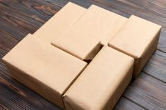 Brown mail package parcel blank for you design. Cardboard box on a dark wooden background.  stock images