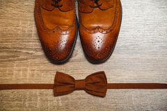 Brown male shoes and brown bow tie. On the wooden background Stock Images