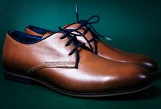 Brown male shoes. In green background Royalty Free Stock Photography