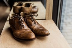 Brown male shoes at showcase in shop. Modern brown male shoes at showcase in shop Stock Photo