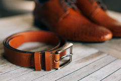 Brown man`s shoes with laces on a wooden background and a brown. Belt Royalty Free Stock Images