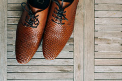 Brown man shoes with laces on wooden background. Brown man`s shoes with laces on a wooden background Stock Photography