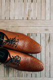 Brown man shoes with laces on wooden background. Brown man`s shoes with laces on a wooden background Stock Images
