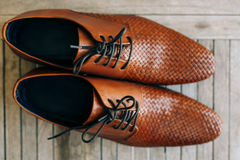 Brown man shoes with laces on wooden background. Brown man`s shoes with laces on a wooden background Royalty Free Stock Photos