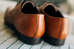 Brown man shoes with laces on wooden background. Brown man`s shoes with laces on a wooden background Stock Image