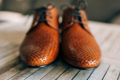 Brown man shoes with laces on wooden background. Brown man`s shoes with laces on a wooden background Royalty Free Stock Photo